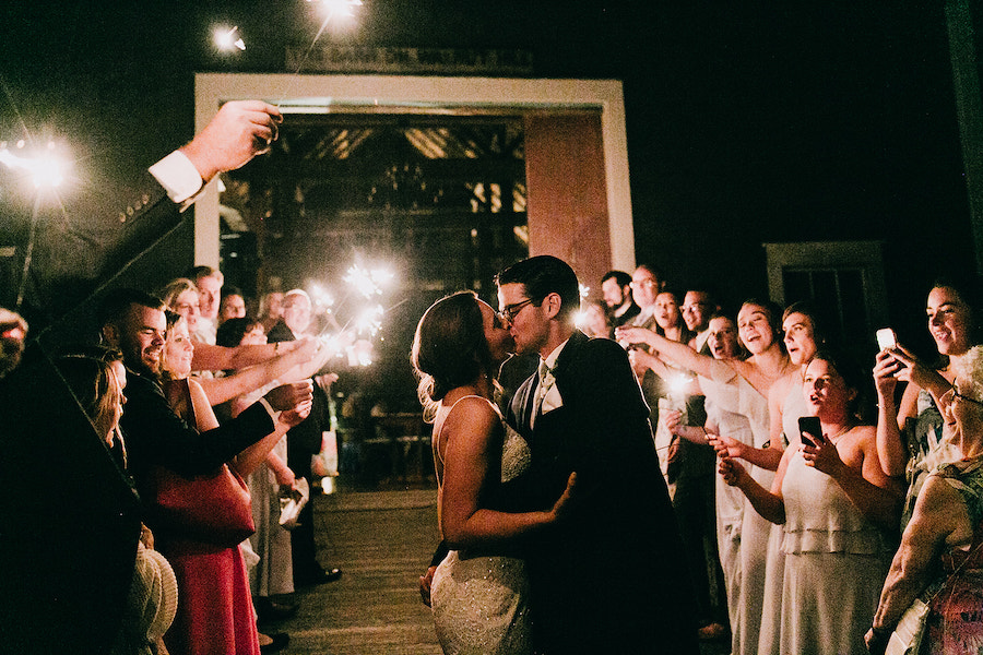 Bride and groom kiss as guests line the walkway with sparklers.
