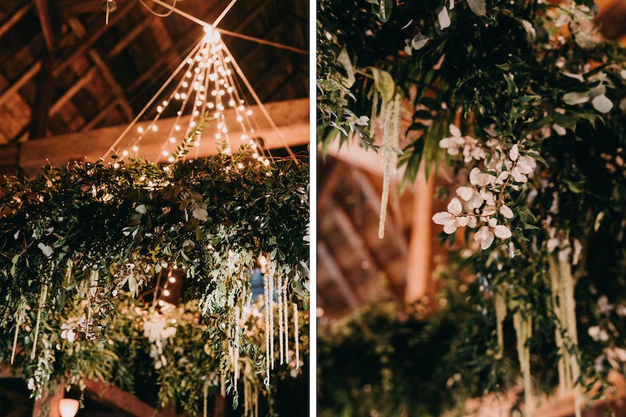 Bespoke floral chandelier suspended from barn ceiling with draping greenery.