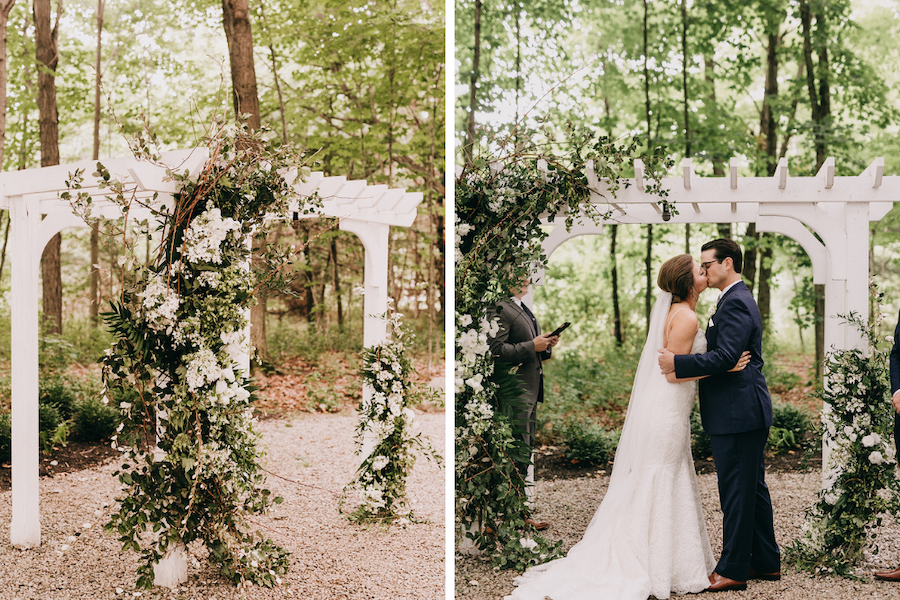 White ceremony arch covered in greenery and white flowers and bride and groom share first kiss.