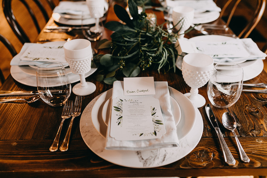 Guest place setting with marble charger and white china with greenery centerpieces.