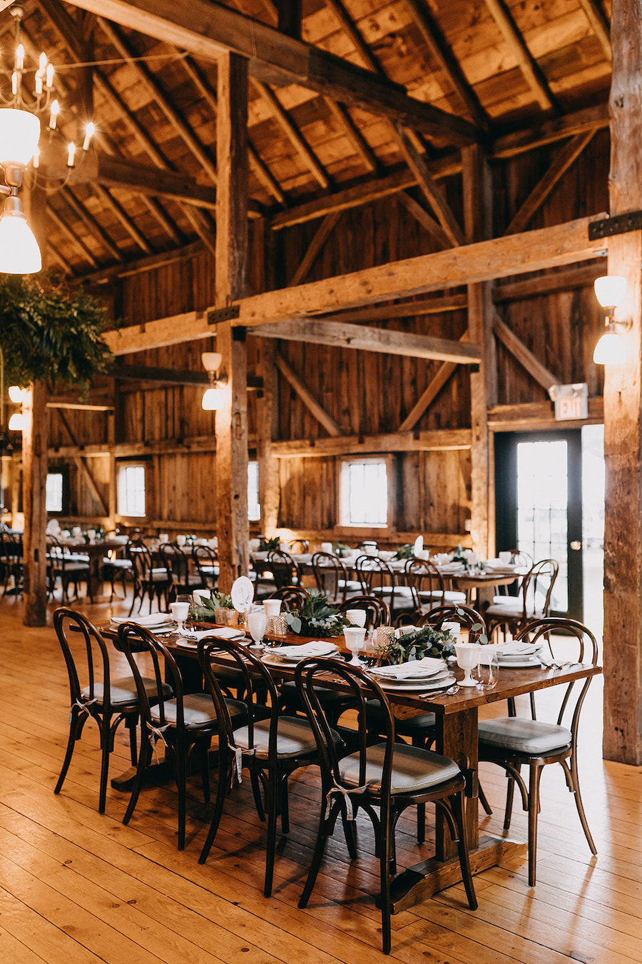Farm tables set with bentwood chairs inside barn reception.