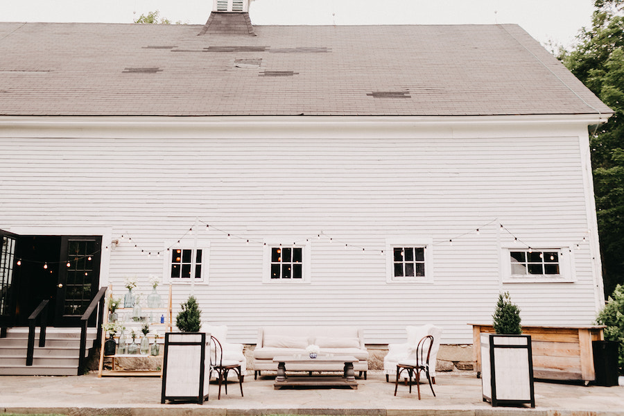 Seating vignette outside The Barn on Walnut Hill with lights strung overhead.