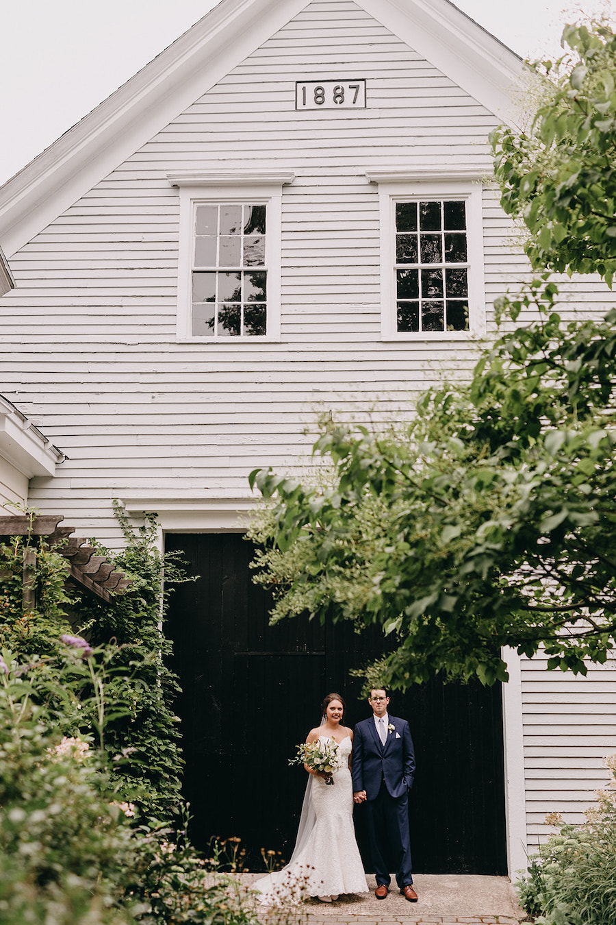 Newlyweds hand in hand in front of barn as seen on Tacari Weddings.