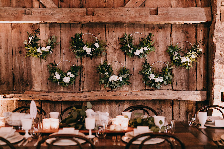 Floral hoop bouquets hanging from barn walls at reception.