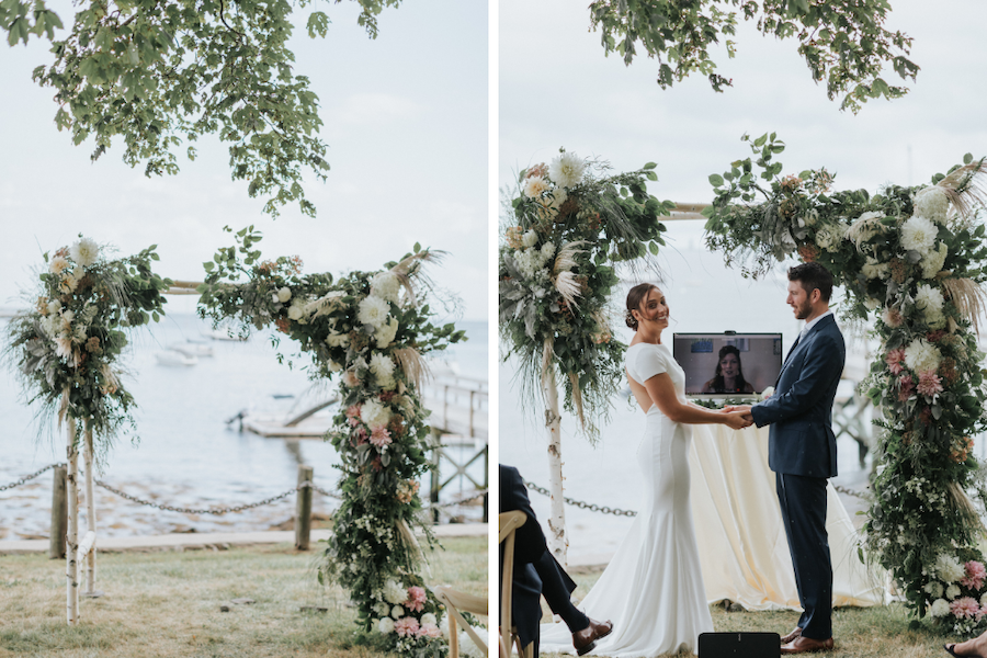 Bride and groom exchange vows before a floral adorned structure with the ocean in the background.