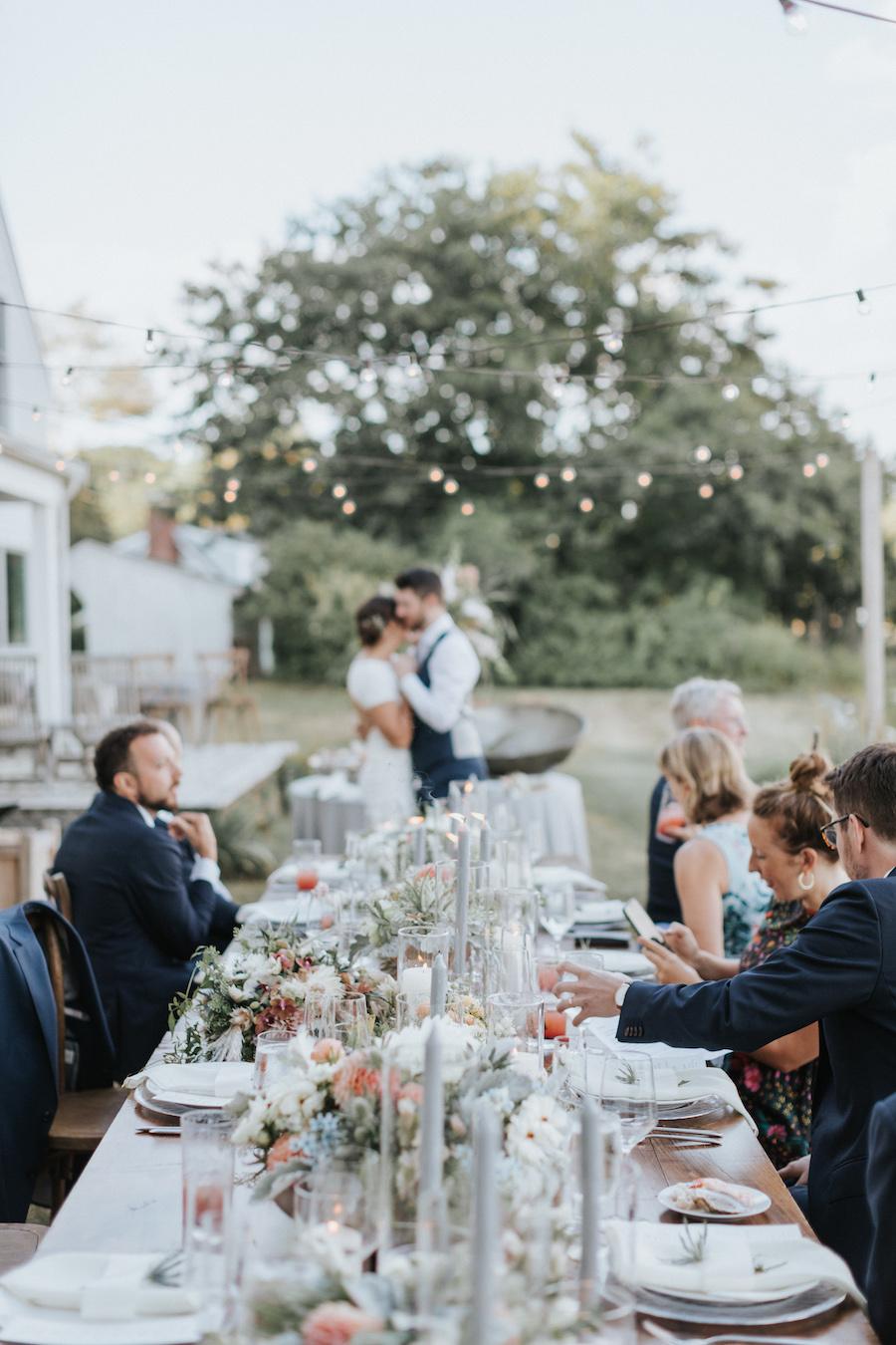 Newlyweds share first dance beneath lights strung overhead in alfresco reception.