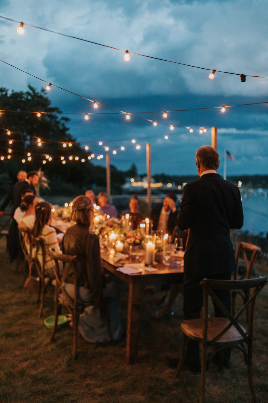 Guest gives toast to the newlyweds as the sun sets and candlelight glows.