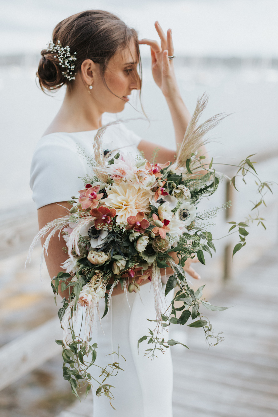 Bride stand on dock with loose bohemian floral bouquet.