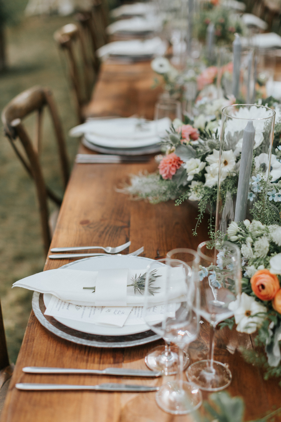 Close up shot of floral filled tablescape on wooden farm tables.