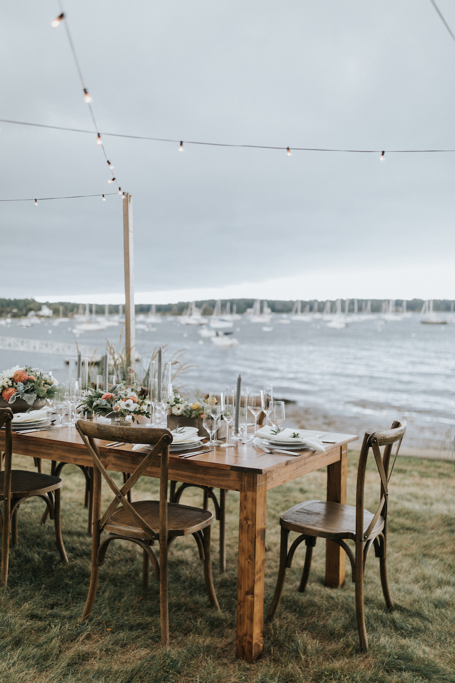 Wooden farm tables set with china and flowers beneath string lighting on the coast.