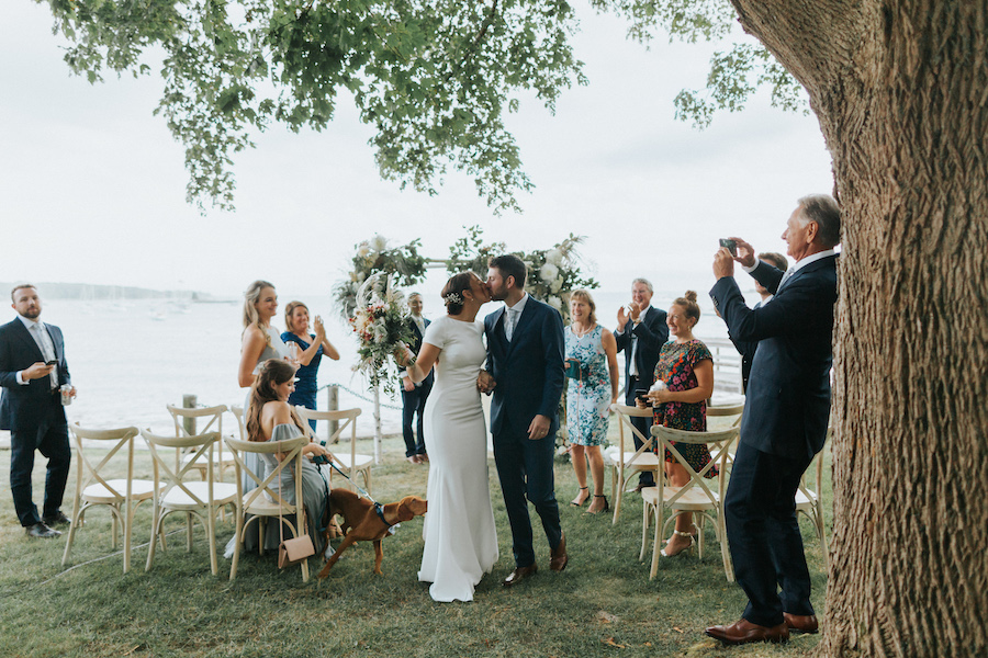 Newlyweds kiss at the end of the aisle while guests cheer.