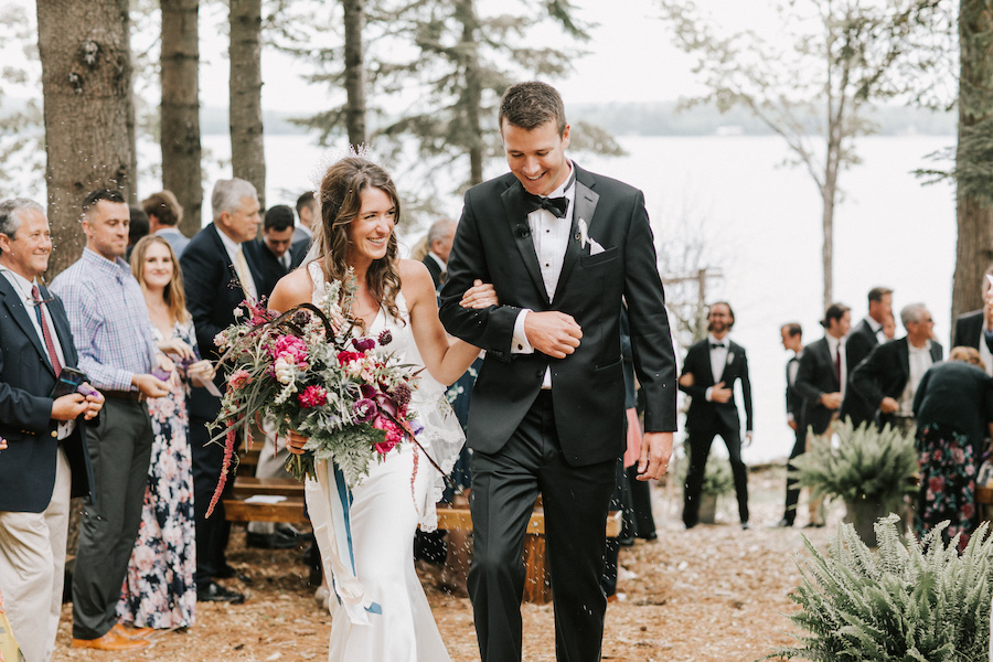 Newlyweds walk down the aisle arm in arm.