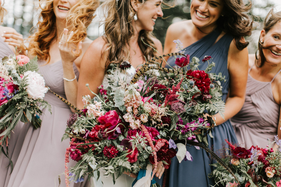 Bridal party gathers together with their colorful floral bouquets.