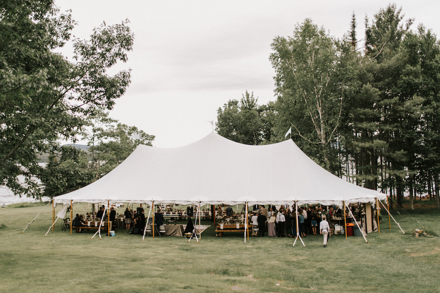 Guests dine beneath sailcloth tent set in Maine forest.