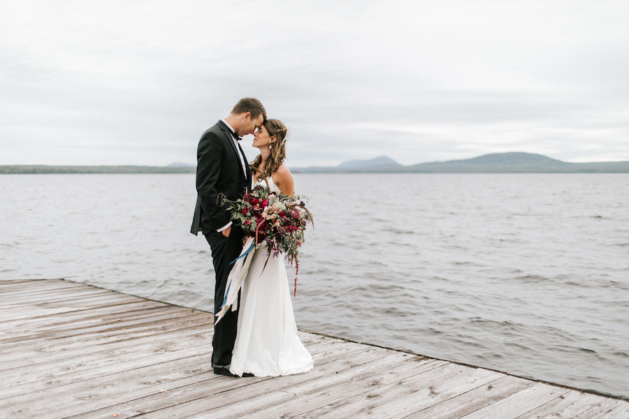 Newlyweds embrace on dock in lakeside wedding.