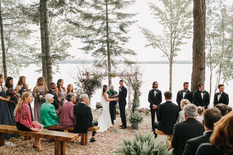 Bride and groom exchange vows in lakeside wedding.